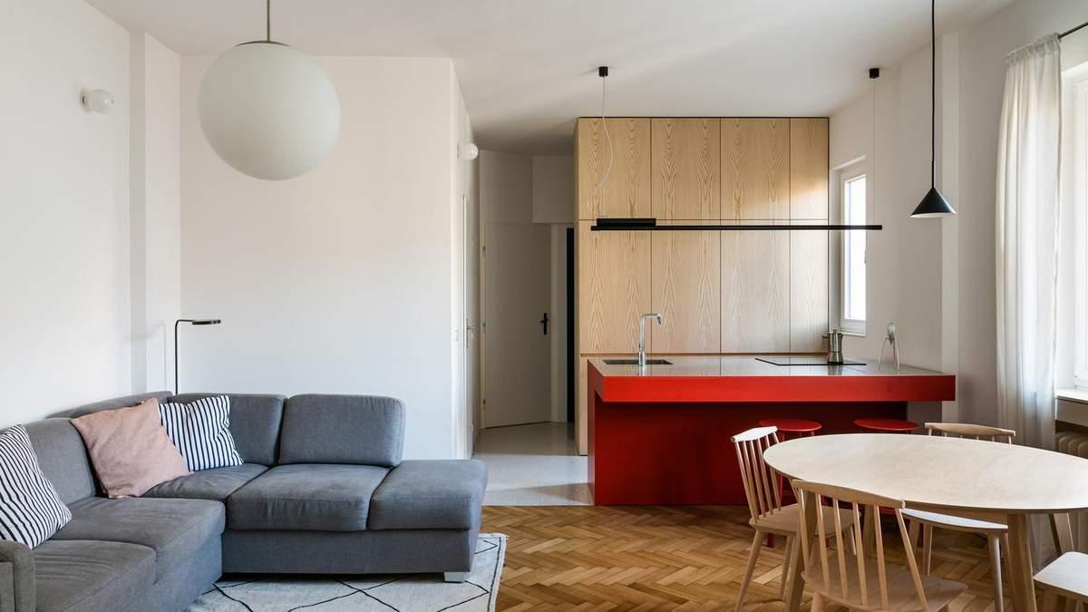 У вітальні погляд приковує до себе яскравий червоний стіл