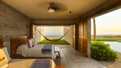 Дерево и солома: как выглядит интерьер просторного дома на берегу океана – фото